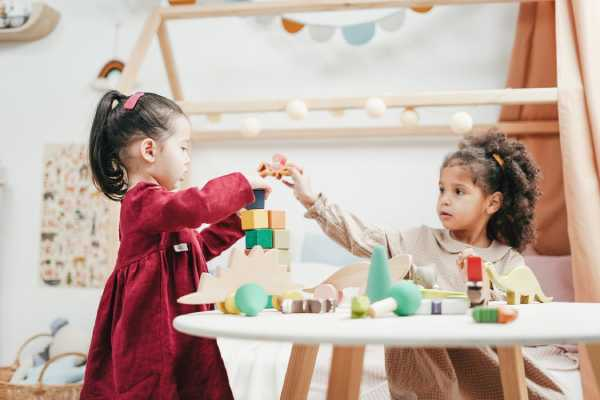 two young girls playing with blocks at a table