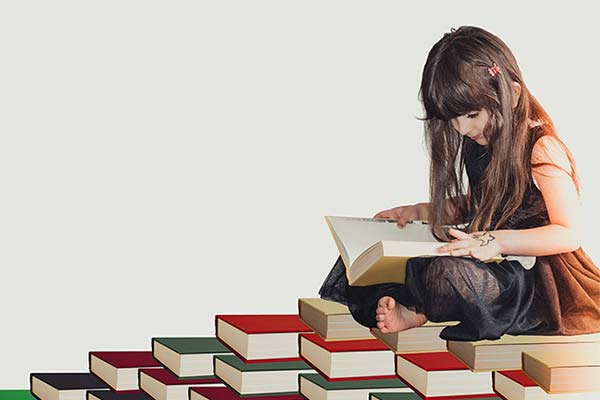 young girl with long hair sitting on a pile of books
