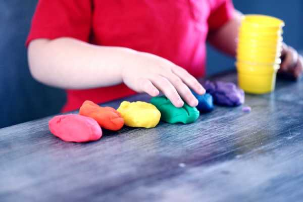 young boy wearing a red shirt playing with play dough