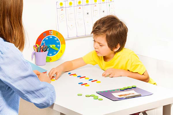 young boy in a yellow shirt working with a woman in a blue shirt on a puzzle