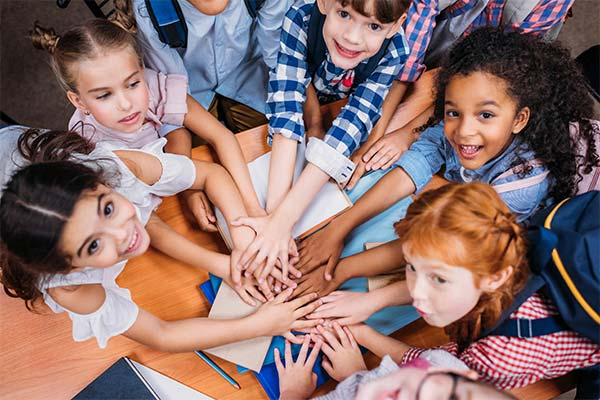 group of smiling kids with their hands together