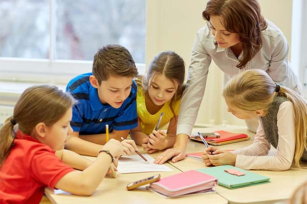 teacher helping four students with a paper